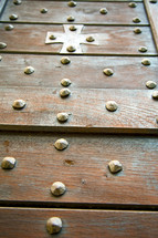 brass cross on a wood door
