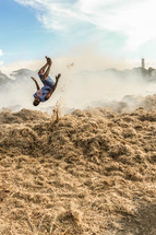 man doing a flip in a burning field in Haiti