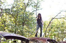 woman standing on old rusted cars in a junk yard