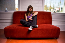 college girl sitting on a red couch