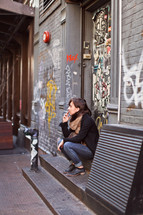 woman siting in front of a graffiti covered wall smoking a cigarette