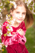 a little girl behind spring blossoms on a branch