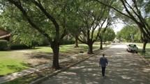 man walking down the street in a neighborhood