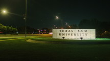 Timelapse of traffic moving around the Texas A&M University campus sign at night.