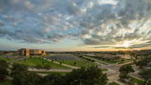 Timelapse of sunset over traffic surrounding an arena.