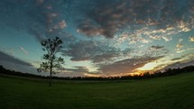 Timelapse of cloud movement and sunset over the countryside.