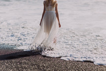 a woman in a flowing sheer dress standing in the tide of the ocean