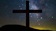 Timelapse of cloud and star movement  over a silhouette of a cross on a hill.