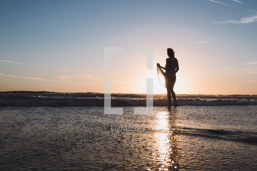 young woman walking on wet sand on a beach at sunset