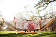 man and woman kissing on a hammock