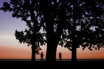 Two people standing beside a large tree at sunset