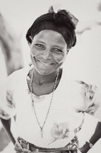 Smiling woman with head scarf and key necklace.