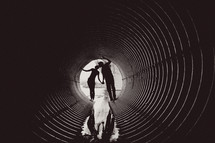 man and woman kissing in a drain pipe tunnel