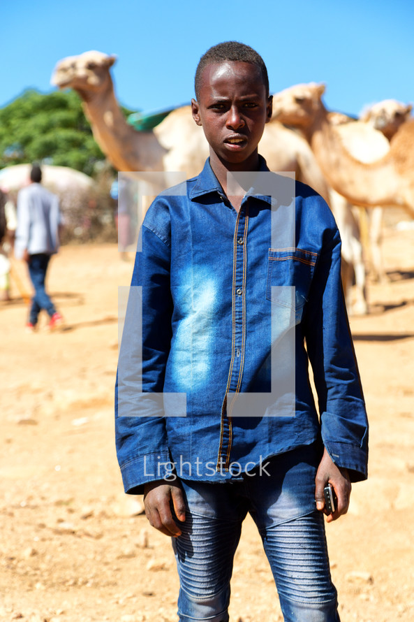 a young boy standing in a market near camels in Ethiopia