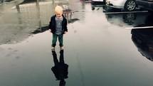 toddler boy splashing in a puddle