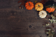 Fall Thanksgiving Holiday Background with Pumpkins, Leaves and Squash Over Wood