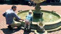 father and son playing in a fountain