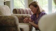 a woman kneeling in prayer in her living room