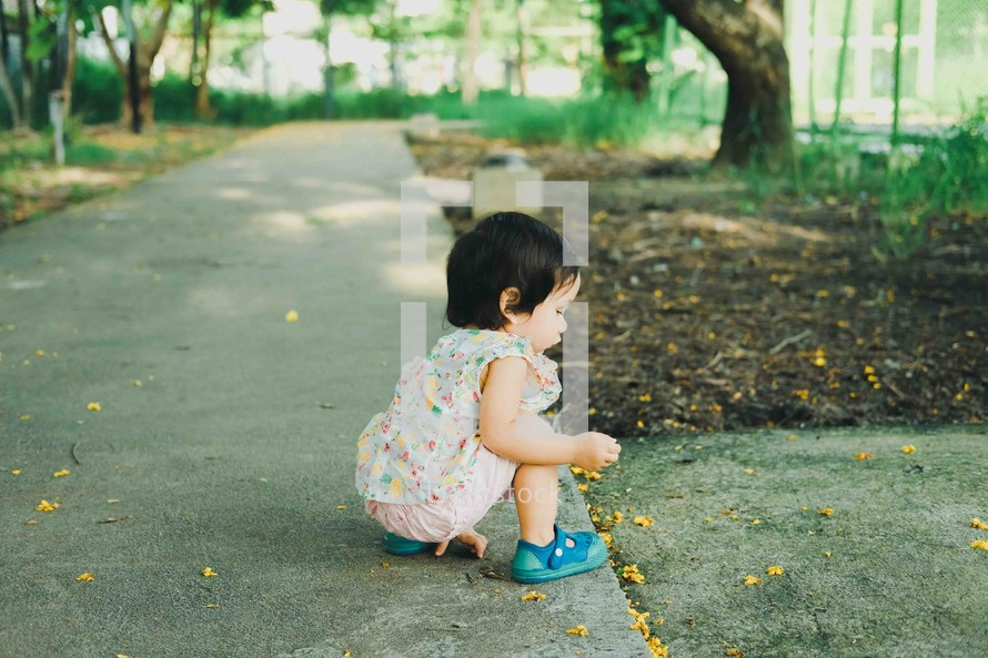 curious toddler picking up a leaf