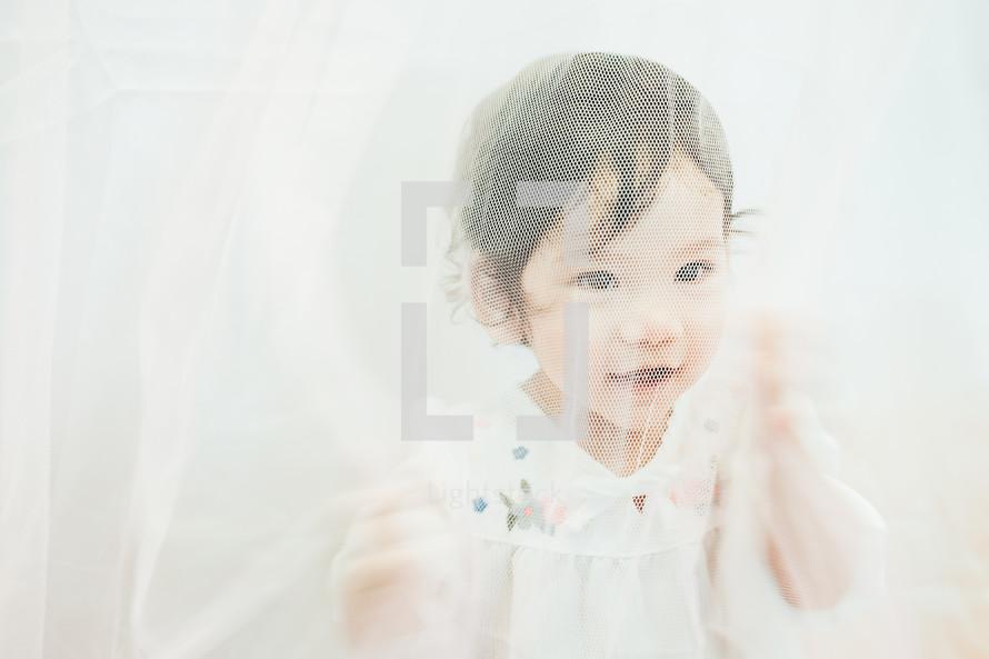 toddler behind a mesh net