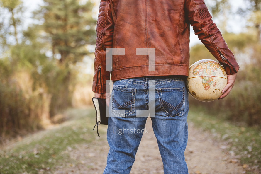 man holding a globe and Bible