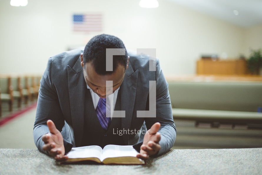 a man reading a Bible at an altar of a church