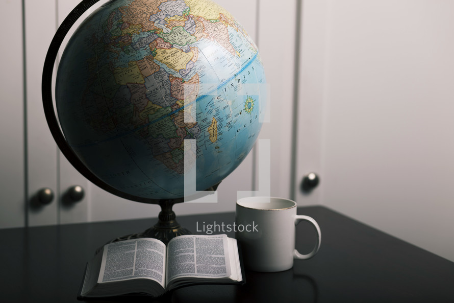 globe, open Bible, coffee mug on a desk