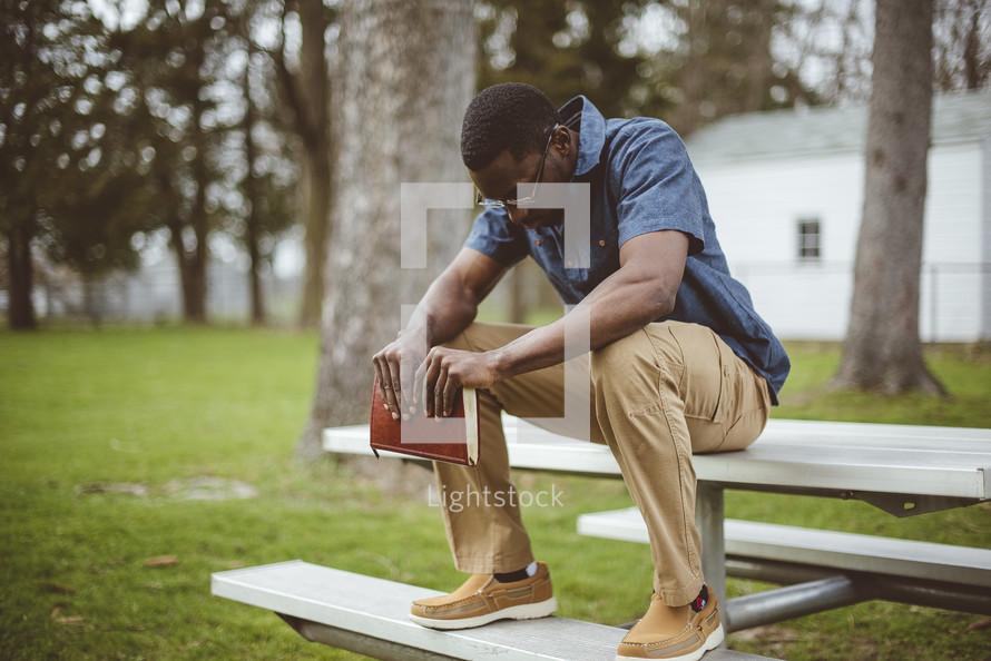 a man sitting holding a Bible praying