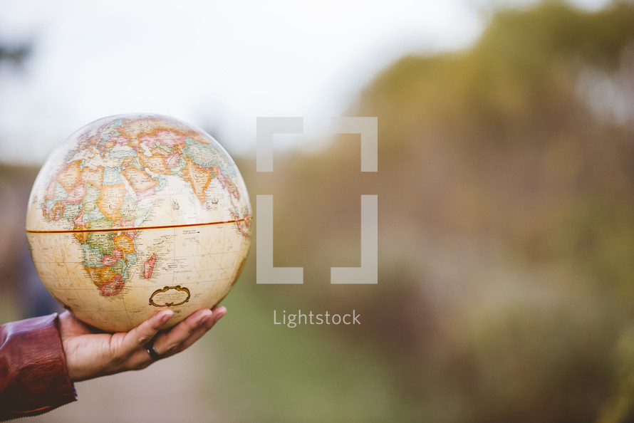 arm holding out a globe