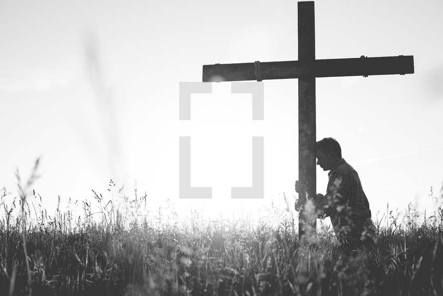 a man standing in a field next to a cross praying
