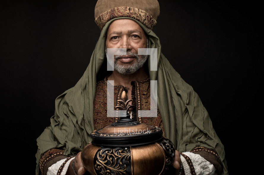 a wiseman holding a gift of frankincense
