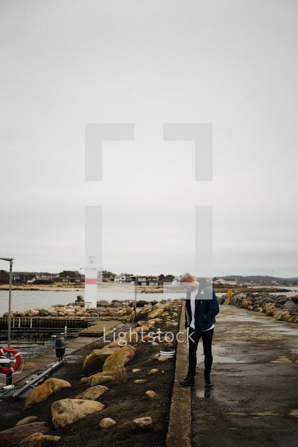 bearded man standing along a shore