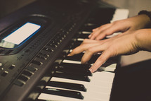 hands on a digital piano