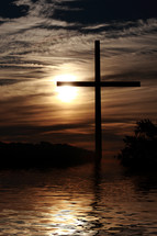 a cross by a lake at sunset