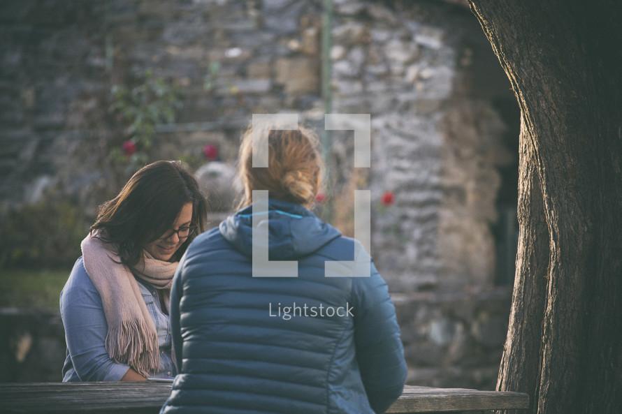 women sitting at a picnic table praying