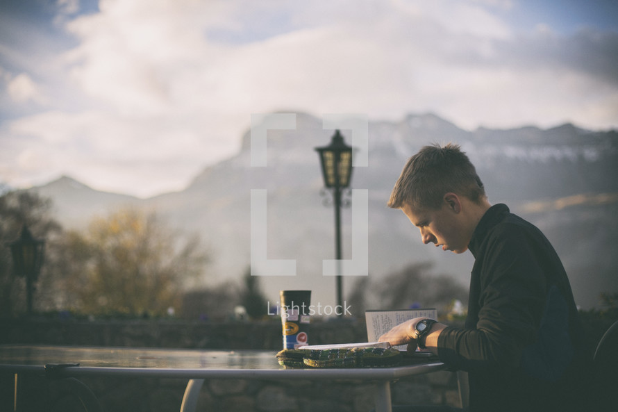 a man reading a Bible at an outdoor table