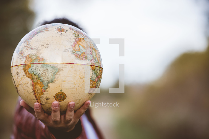 man holding a globe outdoors