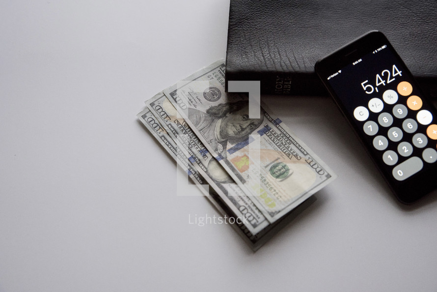 money, calculator app, and Bible on a white background