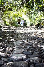 people walking down a rocky trail