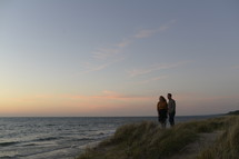 couple standing on a beach in the evening in fall
