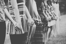 Line of women holding hands while standing in a field.