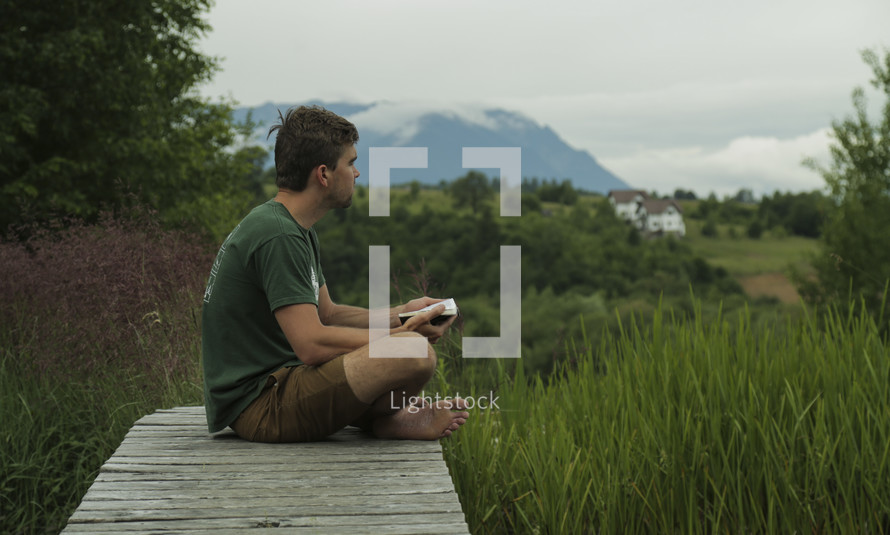a man reading outdoors with a scenic view