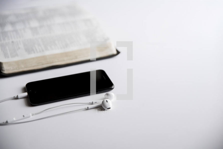 earbuds, cellphone, and Bible