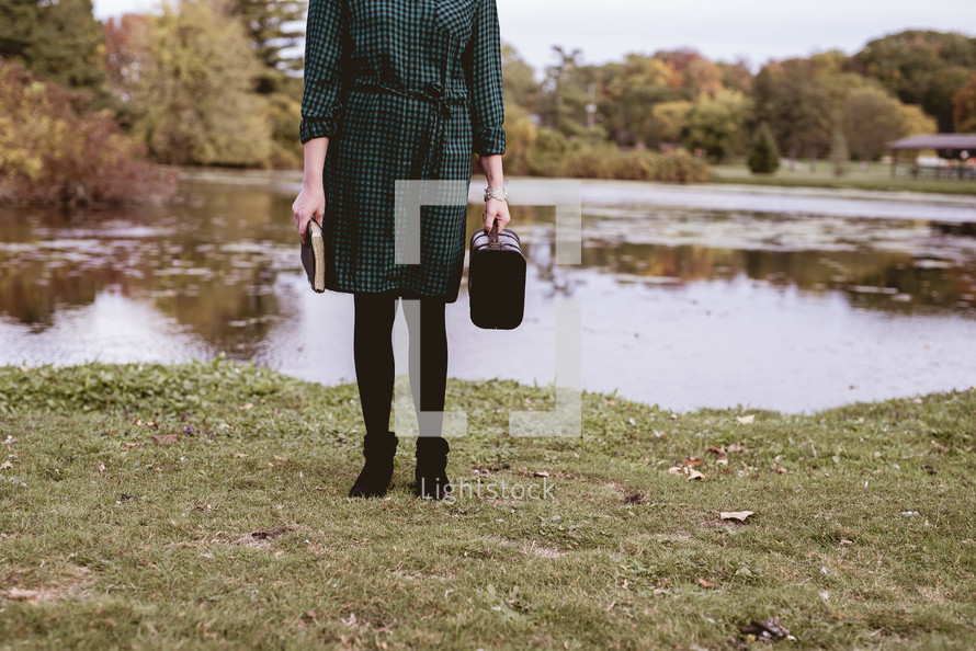a woman holding a suitcase and Bible