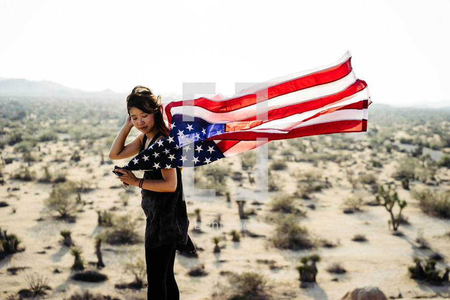 A woman holding an American flag in a desert