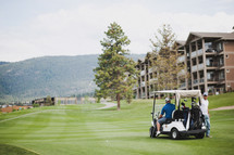 golf cart and golfers on a golf course