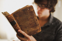 A teenager reading a vintage book