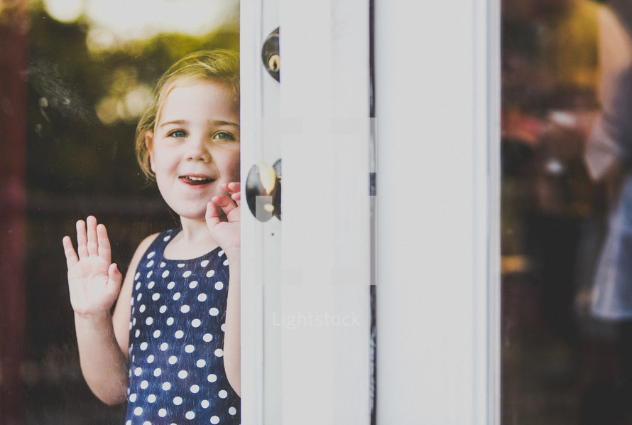 toddler girl looking out a glass door