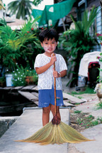 little Thai boy with a broom