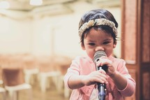 toddler girl holding a microphone